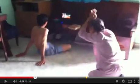 Hình ảnh cắt từ clip cho thấy người mẹ già liên tục quỳ lạy van xin con năm 2014.
