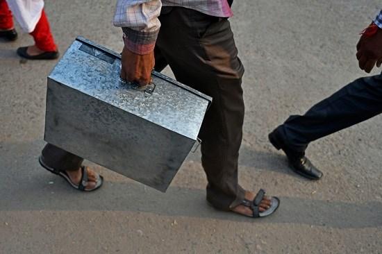Một người đàn ông Ấn Độ xách cả hòm tiền đi đổi.