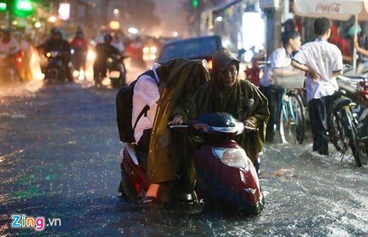 Khoảnh khắc người mẹ dắt con ngồi trên xe qua nơi nước ngập ở TP.HCM của tác giả Trần Ngô Hải An làm lay động trái tim bạn trẻ. Tình yêu thương, sự che trở, đùm bọc hy sinh của mẹ dành cho con là vô bờ bến. Ảnh: Hải An.