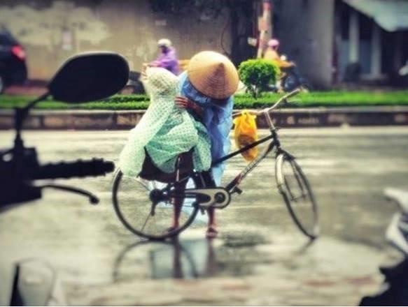 Ngày 15/8, diễn đàn hơn 200.000 thành viên chia sẻ bức ảnh trong cơn mưa tầm tã, người mẹ dừng xe đạp, mặc lại áo mưa cho con. Không ít dân mạng đã viết: Hình ảnh thật đẹp giữa đời thường. Ảnh: Phạm Kiên.