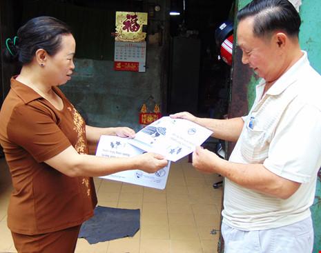 Thành viên Hội Phụ nữ phường 12, quận 11 (bìa trái) phát tài liệu và hướng dẫn một hộ dân cách tìm diệt lăng quăng trong nhà. (Ảnh chụp sáng 20-11) Ảnh: TRẦN NGỌC