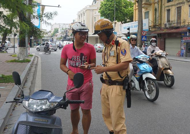 Cảnh sát giao thông Hà Nội đã xử lý nhiều trường hợp vi phạm luật giao thông đường bộ vì mải chơi Pokemon Go. Ảnh: Nguyễn Bình