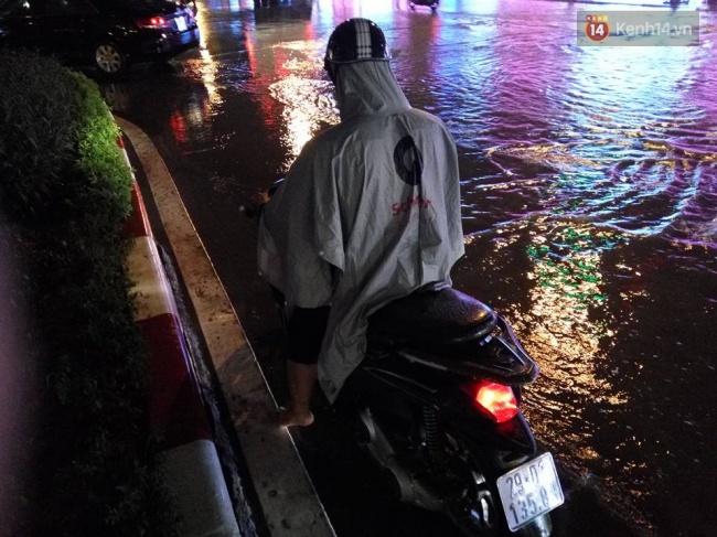 Một người điều khiển xe máy phải tấp vô tránh mưa. Ảnh: Lê Bảo