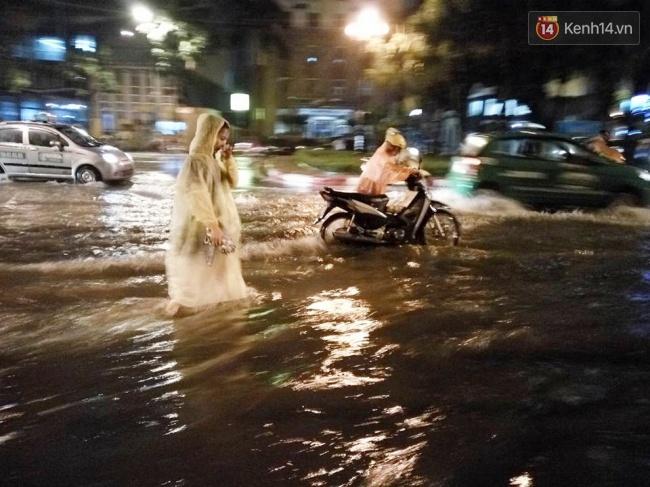 Một người dân phải dắt xe qua đoạn nước ngập sâu. Ảnh: Lê Bảo