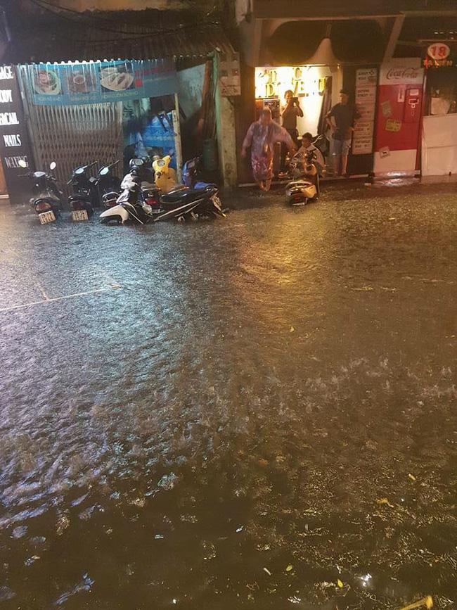 Nhiều tuyến phố nước mưa ngập quá bánh xe, nhiều người phía trú mưa trên vỉa hè không thể di chuyển.