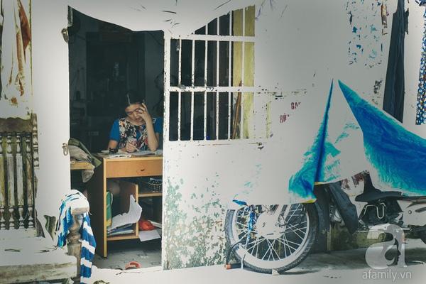 Chị gái Uyên ngồi học bài trước cửa, còn cô em tinh nghịch thì chạy lung tung khắp căn nhà tí hon.