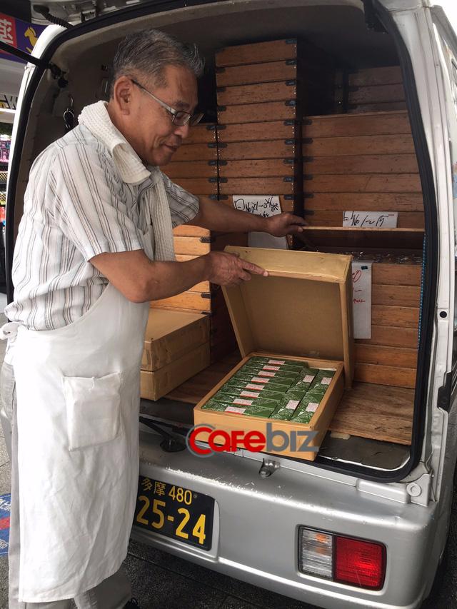 Quản lý cửa hàng bánh nhiệt tình cho khách xem những hộp bánh Yokan mới ra lò được đưa đến cho ngày bán hàng mới.