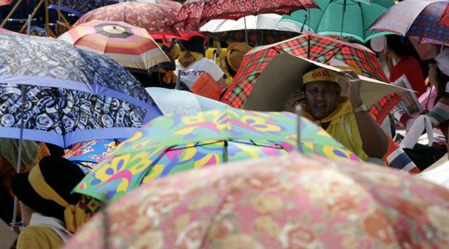 Người dân che nắng đi trên đường ở Thái - Ảnh: Reuters