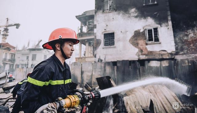 Một lính cứu hoả đang dập lửa trong vụ cháy lán trại vừa qua tại Tân Mai.