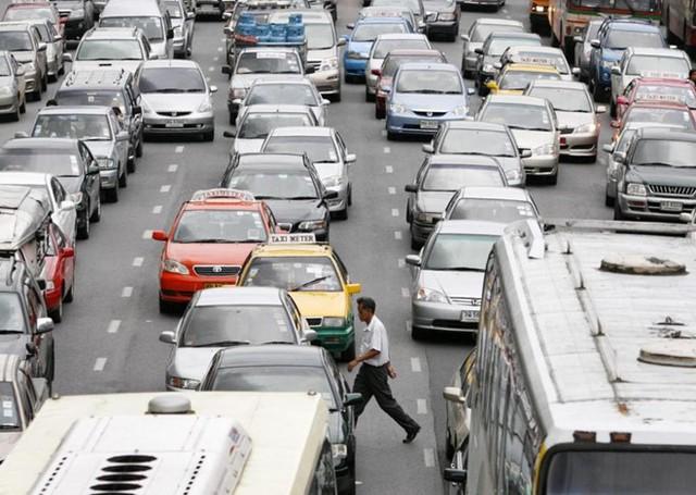 Một người đi bộ qua đường trong lúc xe cộ đều bị tắt lại trong một đám kẹt xe ở Thái Lan. Ảnh: Reuters