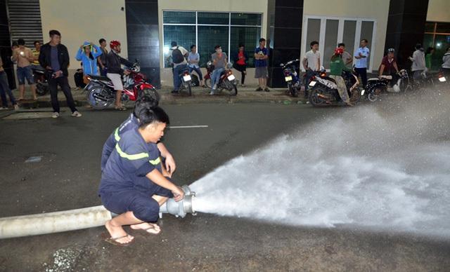 Cảnh sát PCCC quận 1 phải liên tục bơm nước từ bãi xe ra ngoài trong khi hàng trăm người dân chờ đợi suốt đêm để được lấy xe về sửa chữa.
