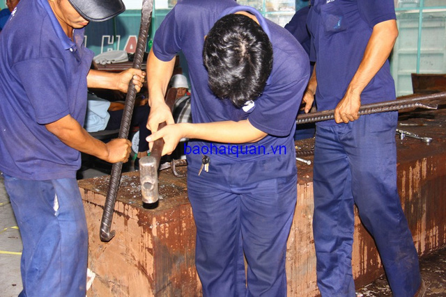 Công nhân bốc xếp phải dùng búa, xà beng mới cạy được nắp khối gỗ. Ảnh: T.H