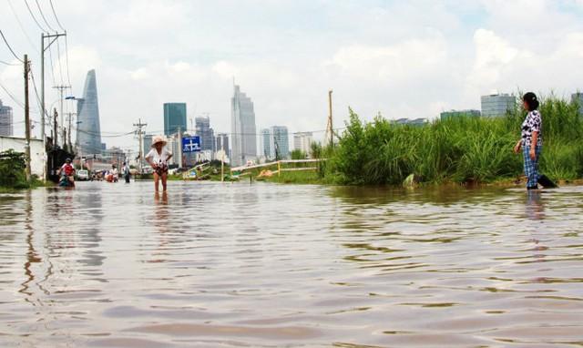 Một bà cụ xắn quần lội nước trên đường Lương Định Của (Quận 2) sáng 27-9 - Ảnh: Lê Phan