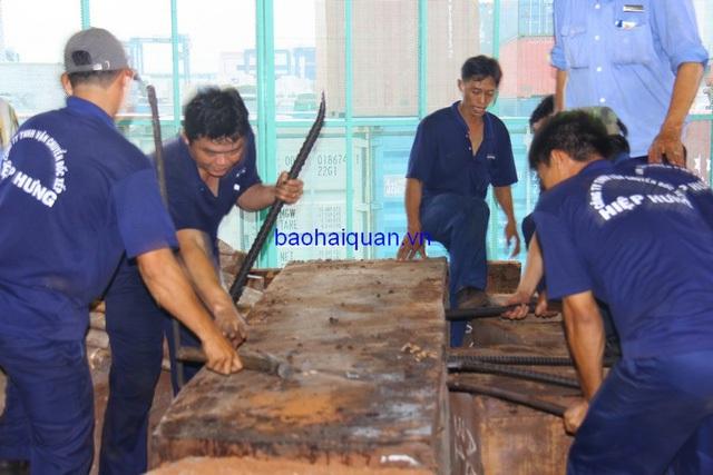 Gần chục người dùng xe beng để phá dỡ khối gỗ. Ảnh: T.H