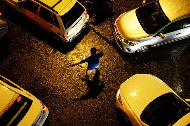 Một thanh niên tả xung hữu đột điều tiết xe cộ lưu thông trên đường sau cơn mưa chiều tối 26-8 - Ảnh: Hữu Khoa