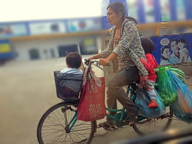 Người mẹ trên chiếc xe đạp cũ kỹ mang theo hai con nhỏ. Bức ảnh truyền tải thông điệp của tác giả: Dù khó khăn vất vả, tình yêu thương của mẹ là bao la. Ảnh: Nguyễn Quốc Hòa.