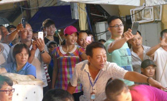 Nhiều người buôn bán, lái xe, bốc vác nhanh chân chạy đến chụp hình Thủ tướng làm kỷ niệm - Ảnh: Lê Kiên- Tuổi trẻ.