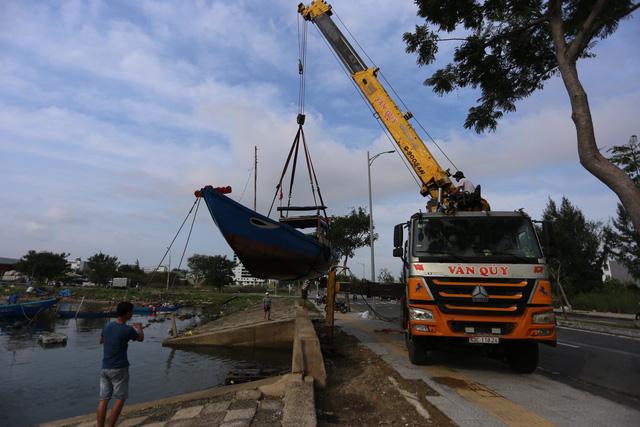 [Ảnh] Xe cẩu tải chở thuyền đến nơi an toàn, công an, bộ đội giúp người Đà Nẵng chằng chống nhà cửa đón bão số 9  - Ảnh 1.