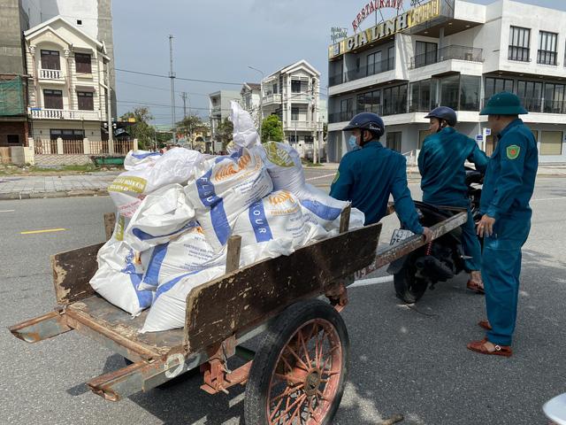 [Ảnh] Xe cẩu tải chở thuyền đến nơi an toàn, công an, bộ đội giúp người Đà Nẵng chằng chống nhà cửa đón bão số 9  - Ảnh 7.