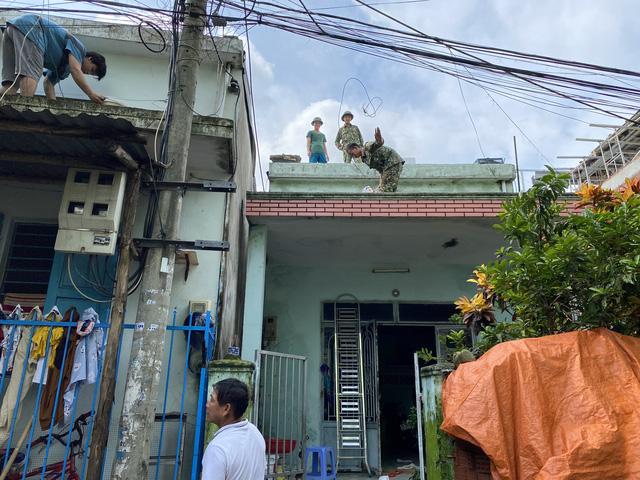 [Ảnh] Xe cẩu tải chở thuyền đến nơi an toàn, công an, bộ đội giúp người Đà Nẵng chằng chống nhà cửa đón bão số 9  - Ảnh 10.