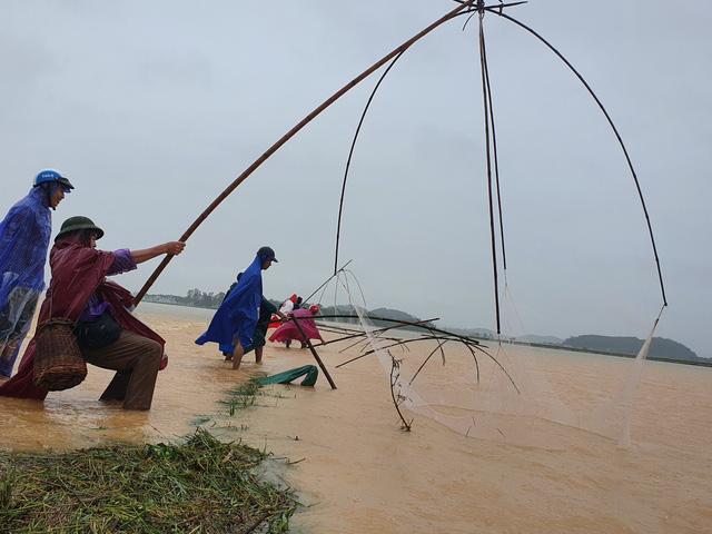 [Ảnh] Cận cảnh điểm sạt lở kinh hoàng chia cắt Quốc lộ 46, dân liều mình đứng giữa dòng lũ bắt cá ở Nghệ An - Ảnh 11.