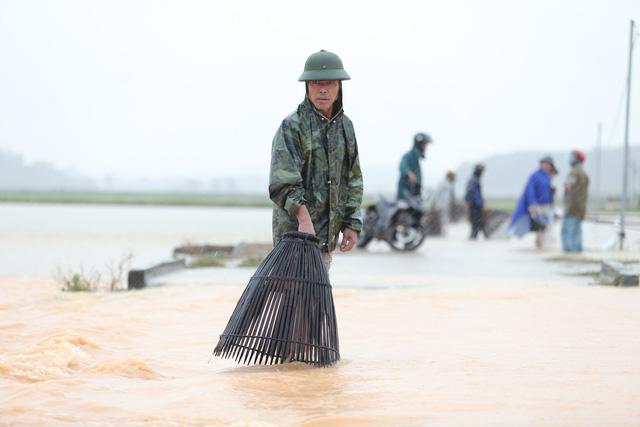 [Ảnh] Cận cảnh điểm sạt lở kinh hoàng chia cắt Quốc lộ 46, dân liều mình đứng giữa dòng lũ bắt cá ở Nghệ An - Ảnh 13.
