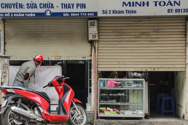 Ảnh: Cửa hàng mở hé cửa, mua bán thò thụt trong những ngày cách ly xã hội - Ảnh 1.