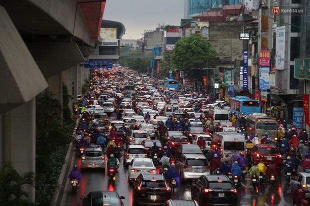 Hà Nội tắc đường kinh hoàng, người dân khổ sở đi làm trong cơn mưa lớn - Ảnh 2.