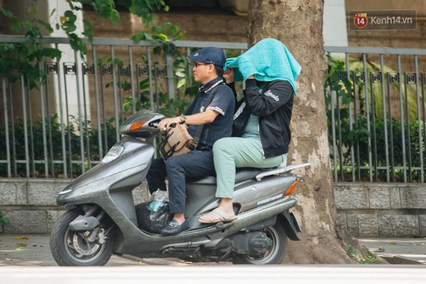 Ảnh: Nhiệt độ ngoài đường tại Hà Nội lên tới 50 độ C, người dân trùm khăn áo kín mít di chuyển trên phố - Ảnh 18.