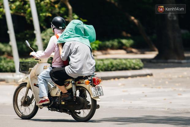 Ảnh: Nhiệt độ ngoài đường tại Hà Nội lên tới 50 độ C, người dân trùm khăn áo kín mít di chuyển trên phố - Ảnh 4.