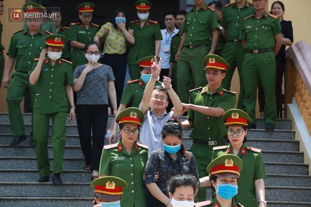Chùm ảnh: Kẻ khóc ngất, người vẫn cười tươi rồi liên tục giơ 2 ngón tay chào gia đình sau khi bị tuyên án vì gian lận điểm thi THPT ở Hòa Bình - Ảnh 6.
