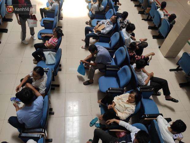 Ảnh: Nắng nóng gần 40 độ C ở Hà Nội, người nhà bệnh nhân vạ vật gần hành lang, dưới bóng cây trong bệnh viện - Ảnh 1.