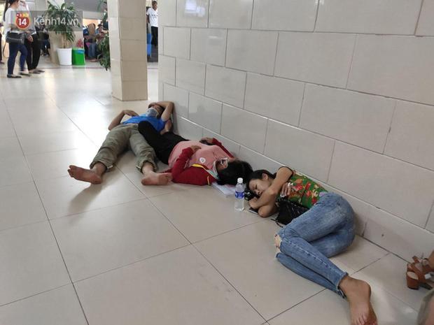 Ảnh: Nắng nóng gần 40 độ C ở Hà Nội, người nhà bệnh nhân vạ vật gần hành lang, dưới bóng cây trong bệnh viện - Ảnh 2.
