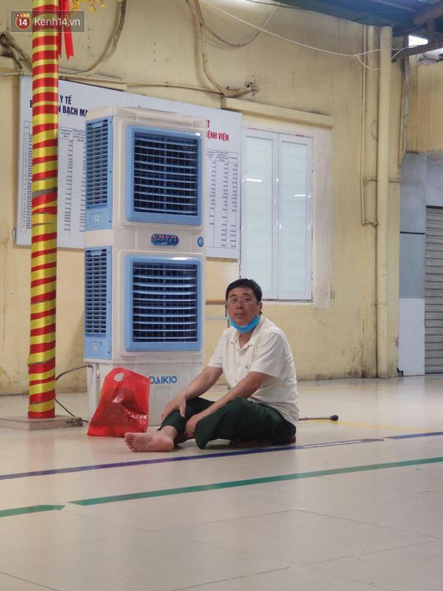 Ảnh: Nắng nóng gần 40 độ C ở Hà Nội, người nhà bệnh nhân vạ vật gần hành lang, dưới bóng cây trong bệnh viện - Ảnh 3.