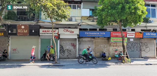 Cảnh tượng trái ngược đến xót xa tại phố lụa sầm uất Hà Nội, lác đác hàng rong nghỉ chân  - Ảnh 1.