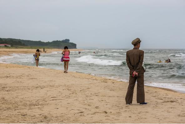 Một người đàn ông mặc quân phục đang giám sát những người đi tắm biển ở Wonsan