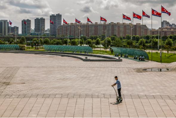 Một người đàn ông chạy xe điện 2 bánh trước khu phức hợp Khoa học Công nghệ ở Bình Nhưỡng