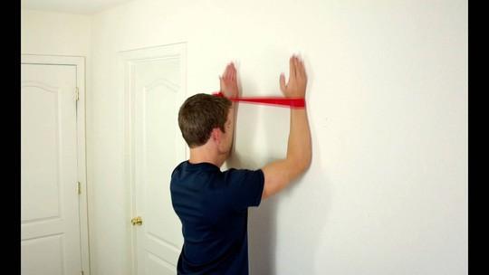 Tư thế khởi động của trượt tường ngược. Thực hiện bằng cách đưa tay lên cao nhất có thể, vẫn giữ lưng thẳng và tay bám sát tường.