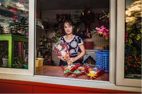 Một người bán hoa trước đài tưởng niệm Mansudae. Người đến đây thường mua hoa để viếng những nhà lãnh đạo Triều Tiên trước đây là Kim Nhật Thành và Kim Jong-il