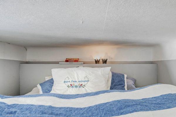 Để tạo không gian riêng tư và yên tĩnh, góc nghỉ ngơi được đưa lên gác xép. Nơi đây bố trí đơn giản với phần kệ đầu giường đặt đèn chiếu sáng và chăn nệm.