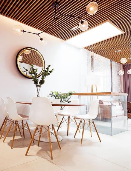 Phòng khách và khu vực bếp, bàn ăn được bố trí chung trong cùng một không gian mở thông thoáng. Toàn bộ trần nhà được làm bằng hệ lam gỗ đắt tiền.