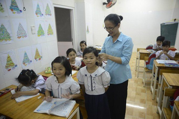 Sơ Hạnh đang buộc lại tóc cho Kim Yến. Kim Phụng đứng bên cạnh và Kim Ngân ngồi phía dưới. Cả 5 chị em các bé đang học ở đây mà chẳng đứa nào có giấy khai sinh. Mới được cha mẹ đưa đến trường năm ngoái nên dù không cùng tuổi ba chị em vẫn ngồi cùng một lớp.