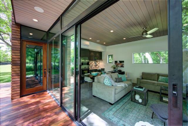 Ngay lối vào là phòng khách thoáng sáng với những bức tường kính cao sát trần khiến tầm nhìn vô cùng đẹp mắt.