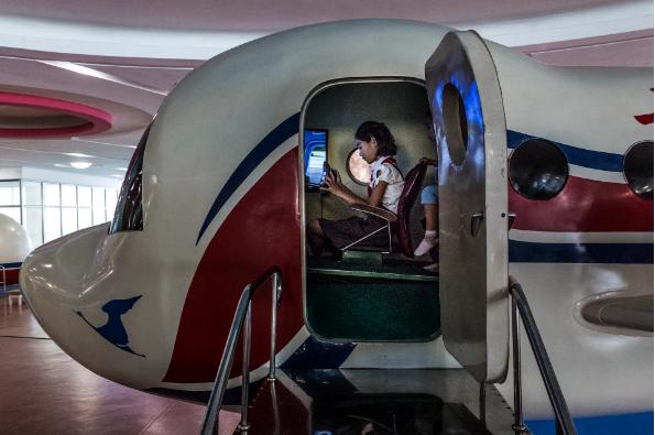 Các bé gái chơi game giả lập tại khu phức hợp Khoa học Công nghệ ở Bình Nhưỡng. Ở đây có một phòng trải nghiệm động đất, phòng thí nghiệm khoa học ảo và các hành lang gắn đầy máy chiếu và màn hình cảm ứng.