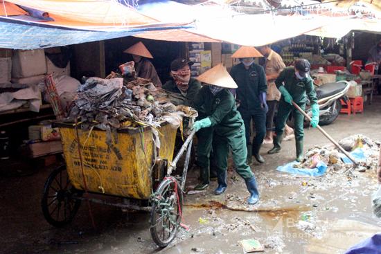Lực lượng dọn vệ sinh gồng mình dọn rác sau mưa lớn tại chợ Vinh. Ảnh: Quang An