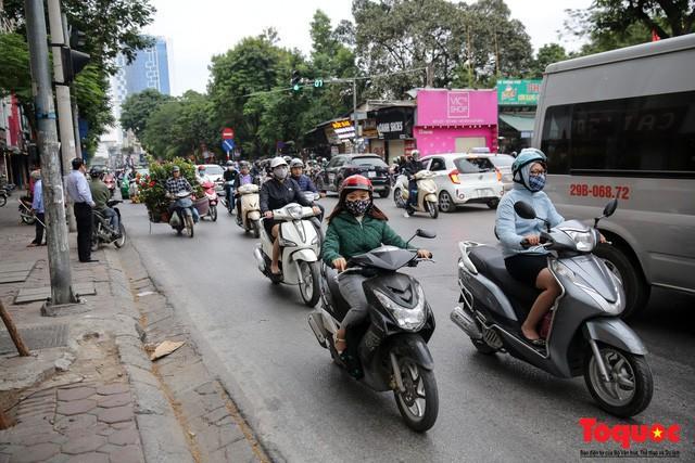 Hình ảnh người dân Hà Nội đón gió lạnh, kẻ đông người hè xuất hiện trên phố - Ảnh 1.