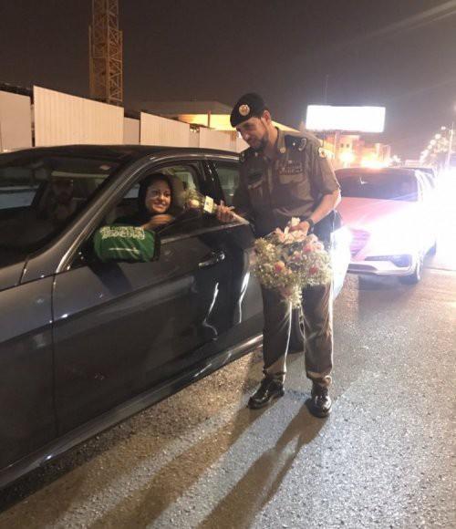 Ả Rập: Các sĩ quan cảnh sát đứng tặng hoa mừng ngày phụ nữ được phép lái xe ra đường - Ảnh 1.