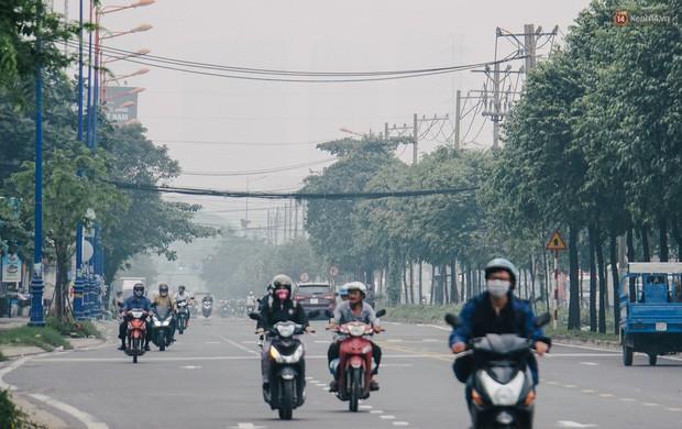 Ảnh: Sài Gòn bị bao phủ một màu trắng đục từ sáng đến trưa, người dân cay mắt khi đi ngoài trời - Ảnh 12.