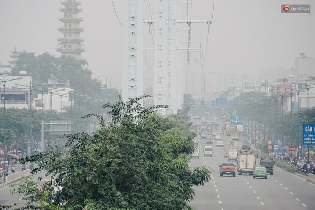 Ảnh: Sài Gòn bị bao phủ một màu trắng đục từ sáng đến trưa, người dân cay mắt khi đi ngoài trời - Ảnh 6.