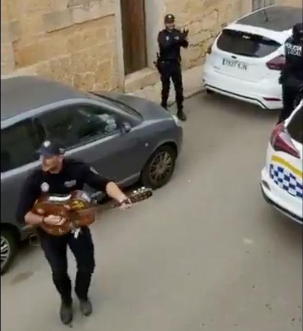 Khoảnh khắc hạnh phúc giữa lúc buồn chán: Anh cảnh sát chơi guitar hát cho cả phố nghe, xua đi bầu không khí u ám vì Covid-19 - Ảnh 1.
